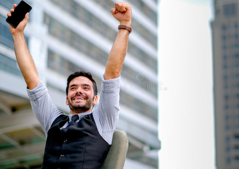 Vit handling för show för affärsman av lyckligt och lyckat vid händer upp med att sitta ner på stol bland staden på dagtid fotografering för bildbyråer