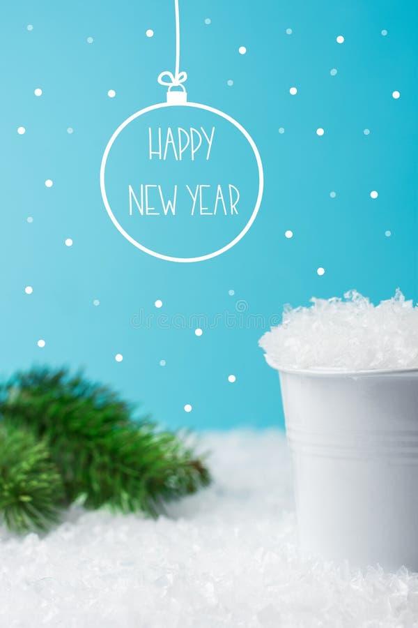 Vit hink som fylls med snögranfilialer i vinterskog på blå bakgrund För klotterjulgran för hand utdragen boll för prydnad royaltyfria bilder