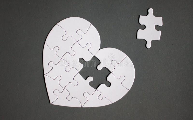 Vit hjärta format pussel med saknaddelen royaltyfri bild