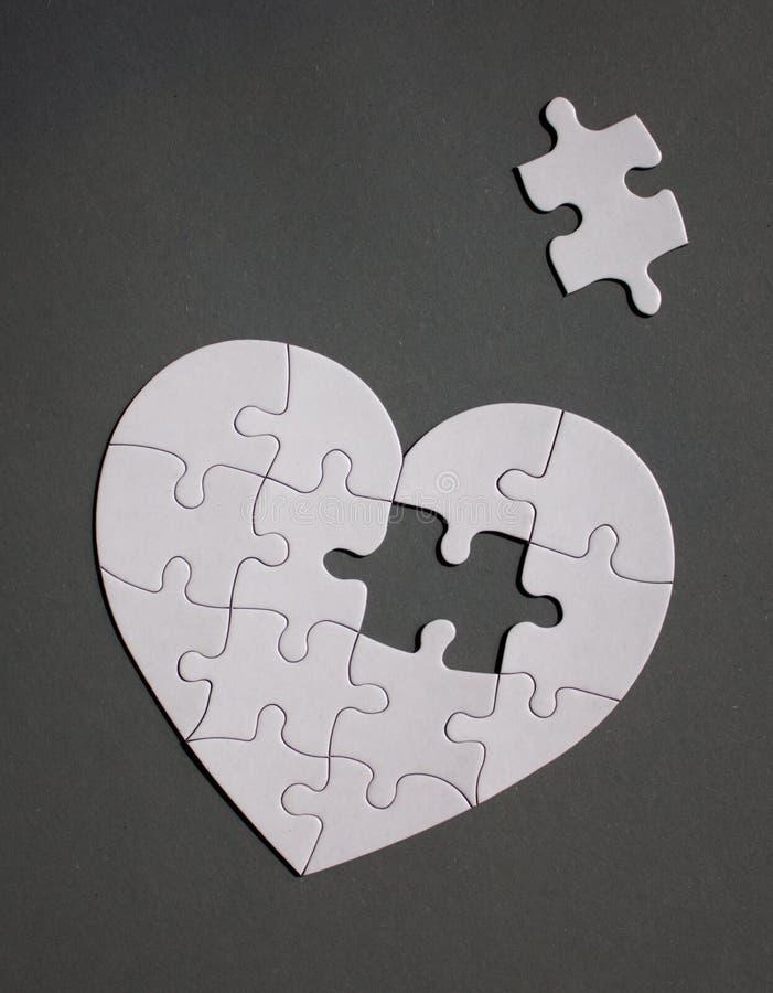 Vit hjärta format pussel med saknaddelen arkivfoton