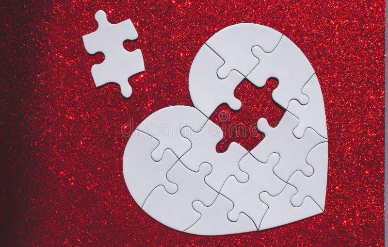 Vit hjärta format pussel på röd gnistrandebakgrund royaltyfri fotografi