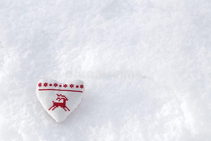 Vit hjärta med hjortar för vinterkorshäftklammer i rött på snö Scandi arkivbild