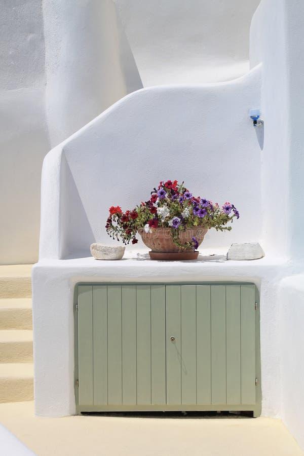 Vit hus och vas med blommor i Santorini, Grekland royaltyfria foton
