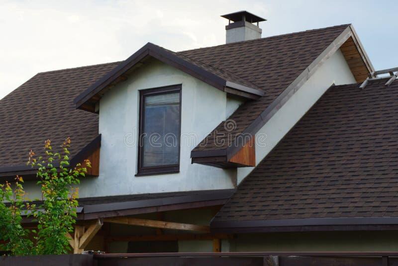 Vit husloft med ett fönster under ett brunt belagt med tegel tak royaltyfri bild