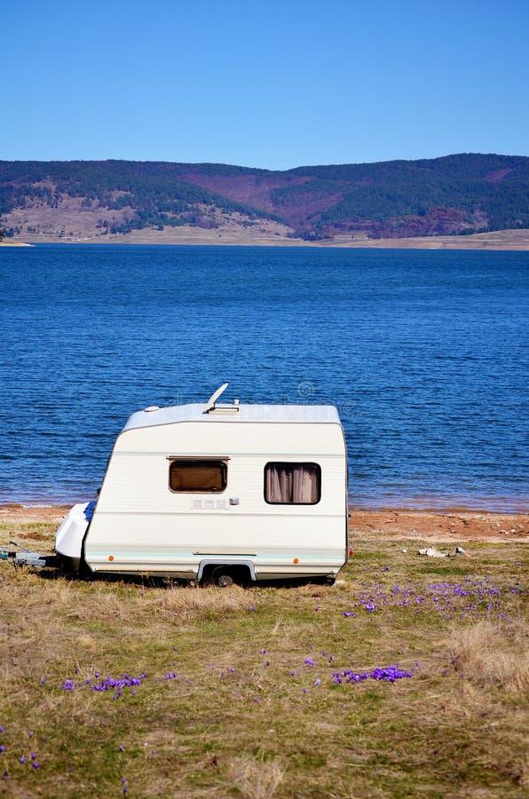 Vit husvagn på en sjöbakgrund arkivbild