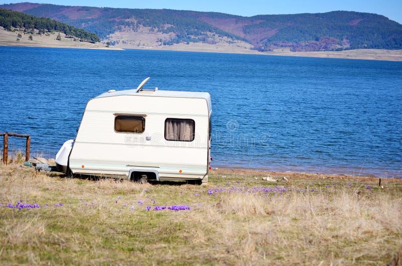 Vit husvagn på en sjöbakgrund royaltyfria bilder