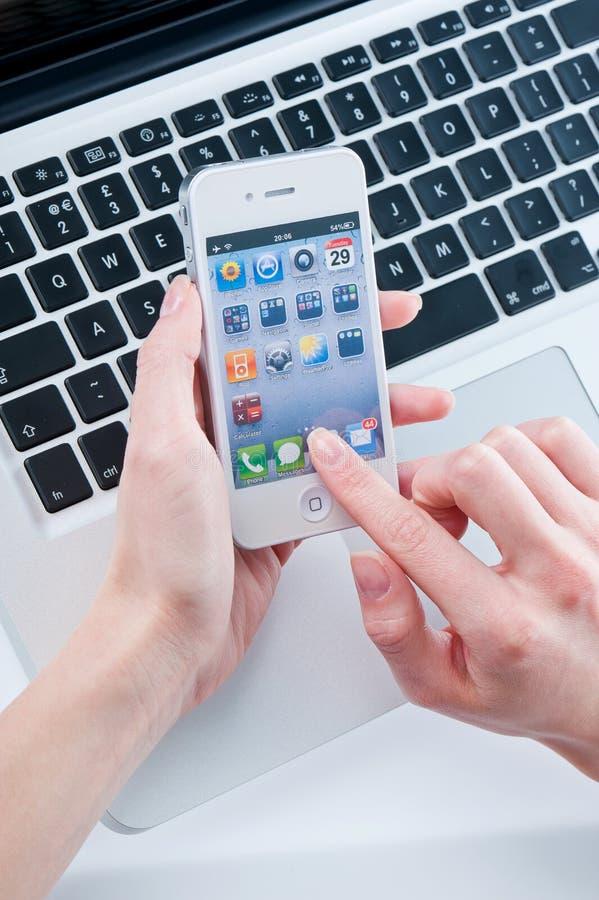 Vit iphone 4 i kvinna händer arkivfoton
