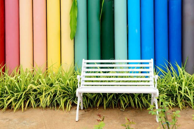 Vit järnbänk och flerfärgat konkret staket royaltyfria bilder