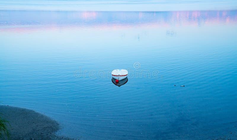Vit jolle som är flytande på lugna blått vatten med reflexion av solnedgångfärger arkivfoto