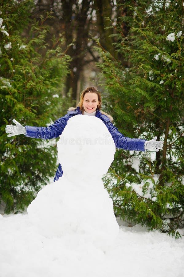 vit jul Den gulliga unga kvinnan bygger en stor snögubbe i parkera arkivbilder