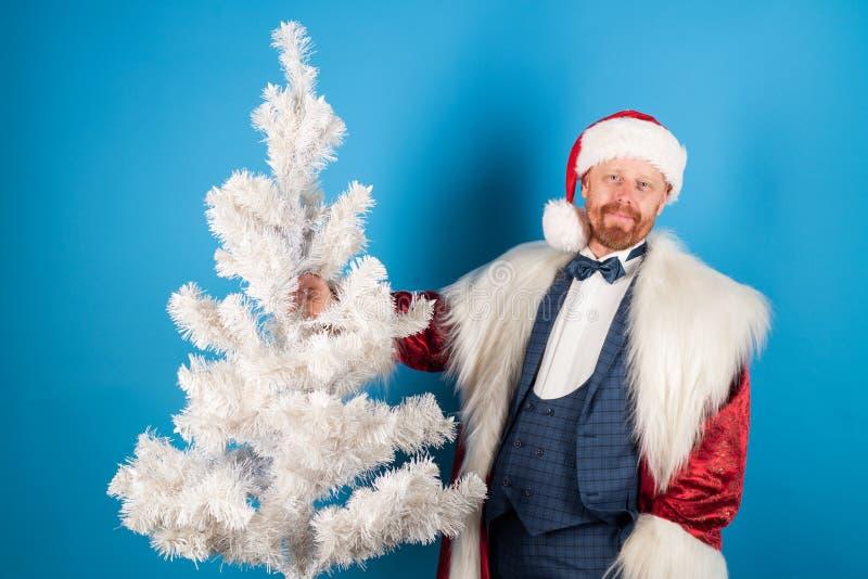 Vit jultree Santa Claus med jul passar Moderna Santa julhelgdagsaftongåvor semestrar många prydnadar lyckligt nytt år Santa på bl arkivbilder