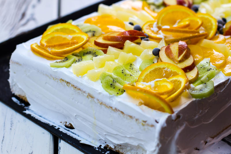 Vit kaka med fruktstycken royaltyfri foto