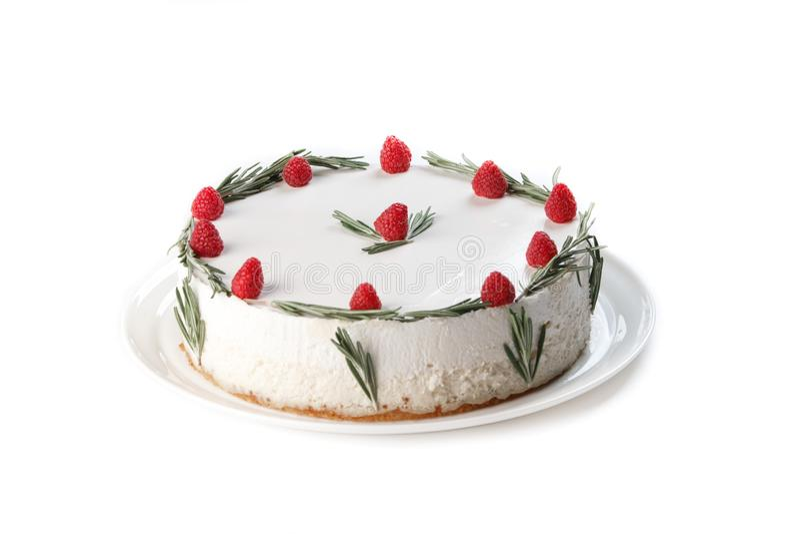 Vit kaka med piskad kräm som dekoreras med hallonet och kvistar av rosmarin på en isolerad vit bakgrund royaltyfria foton