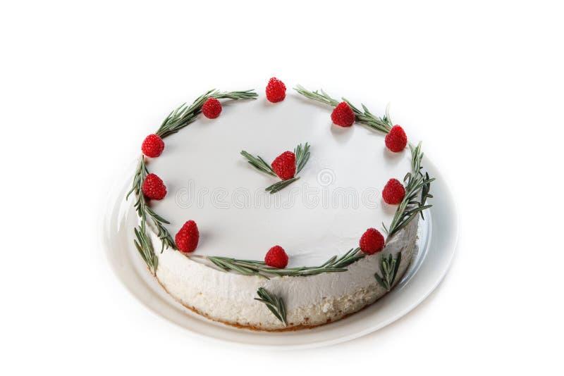 Vit kaka med piskad kr?m som dekoreras med hallonet och kvistar av rosmarin p? en isolerad vit bakgrund royaltyfri bild