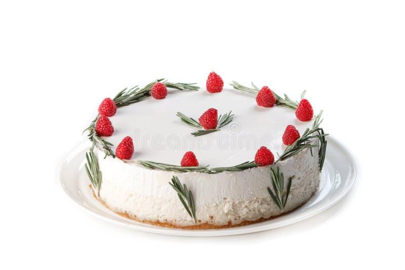 Vit kaka med piskad kr?m som dekoreras med hallonet och kvistar av rosmarin p? en isolerad vit bakgrund royaltyfria foton