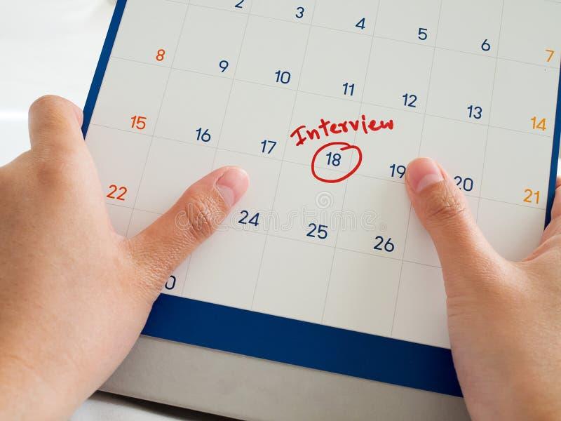 Vit kalender för kvinnahandhåll med det röda intervjuordet som markeras på kalender Viktigt intervjumöte med den potentiella nya  arkivfoton