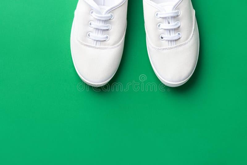 Vit kanfas snörde åt unisex- skor på grön bakgrund Aktiv livsstil för klassiskt tillfälligt för sportskodonungdom mode för tonåri fotografering för bildbyråer