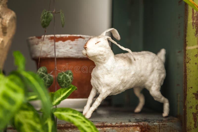 Vit kanin på en textural bakgrund med blommor i trädgården r Kaninslut upp royaltyfria bilder