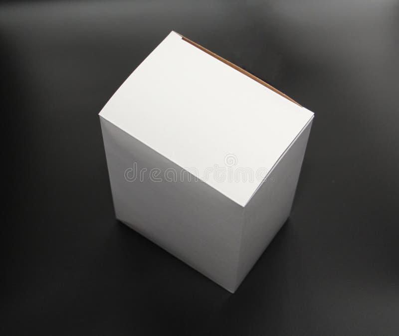 Vit kartong på en svart bakgrund Asken är fyrkantig i form arkivfoto