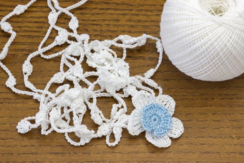 Vit kedja för handgjord virkning och en blå blomma Garnboll för virkning eller handarbete på trätabellen Hemlagad halsband royaltyfri fotografi