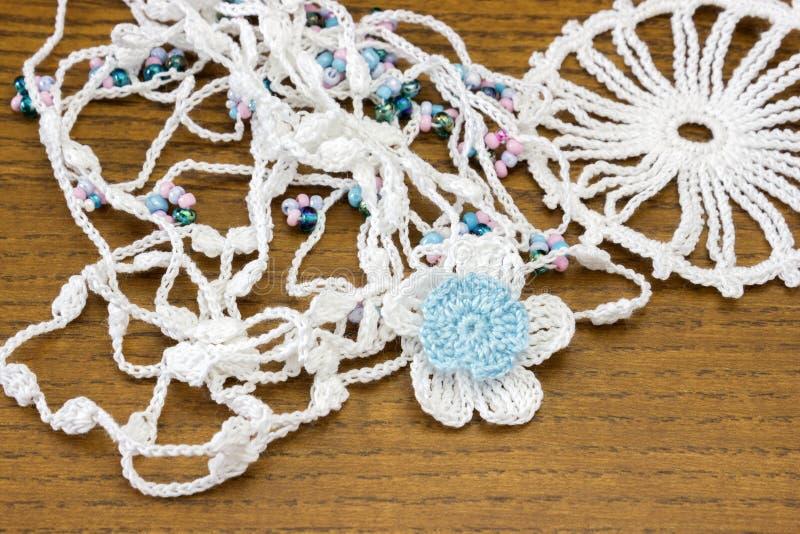 Vit kedja för handgjord virkning och en blå blomma Hemlagad halsband, needlecraft royaltyfri fotografi