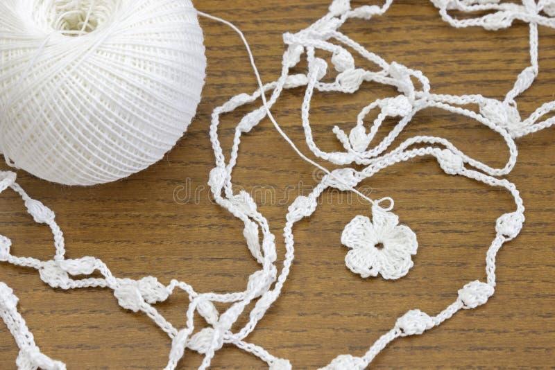 Vit kedja för handgjord virkning och en blomma Garnboll för virkning eller handarbete på trätabellen fotografering för bildbyråer