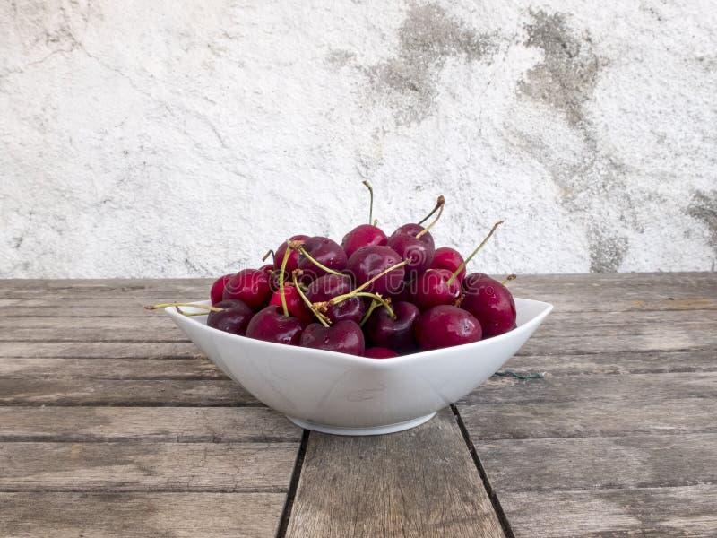 Vit keramisk platta mycket av trätabellen för kvalitets- cherrieson royaltyfri fotografi