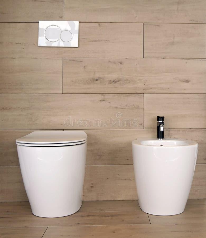 Vit keramisk toalett och bidé i ett badrum som göras av stengodset med träeffekt royaltyfria foton