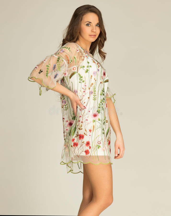 Vit klänning för fantastisk kvinnawearind med blommor royaltyfri bild