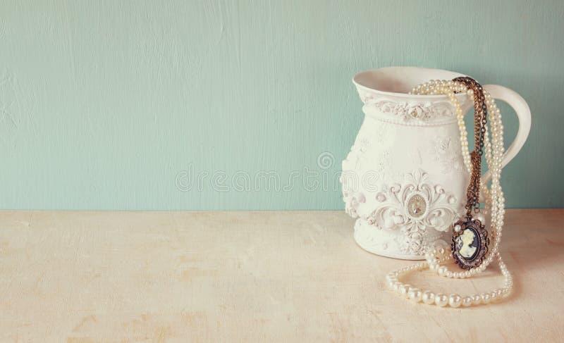 Vit klassisk victorianvas på trätabellen med en samling av romantiska tappningsmycken och pärlor retro filtrerad bild Rum royaltyfria foton