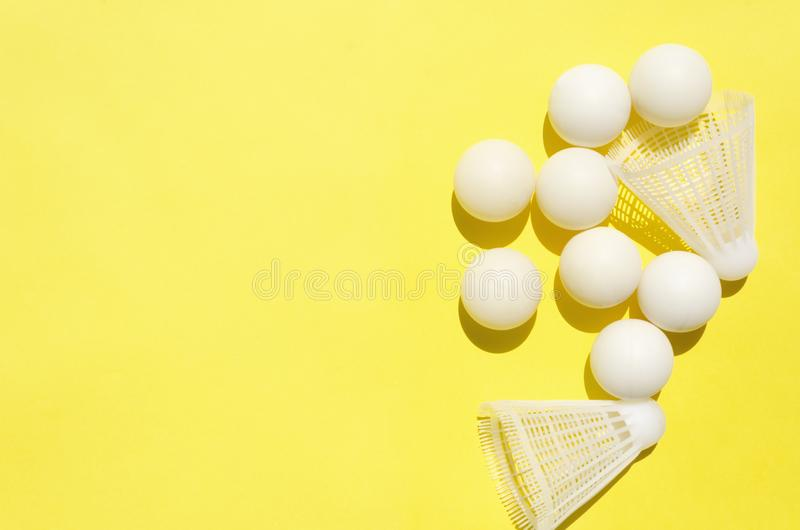 Vit knackar pongbollar och fjäderbollar för badminton på den ljusa gula bakgrunden Begrepp av den aktiva livsstilen och sportar t royaltyfri bild