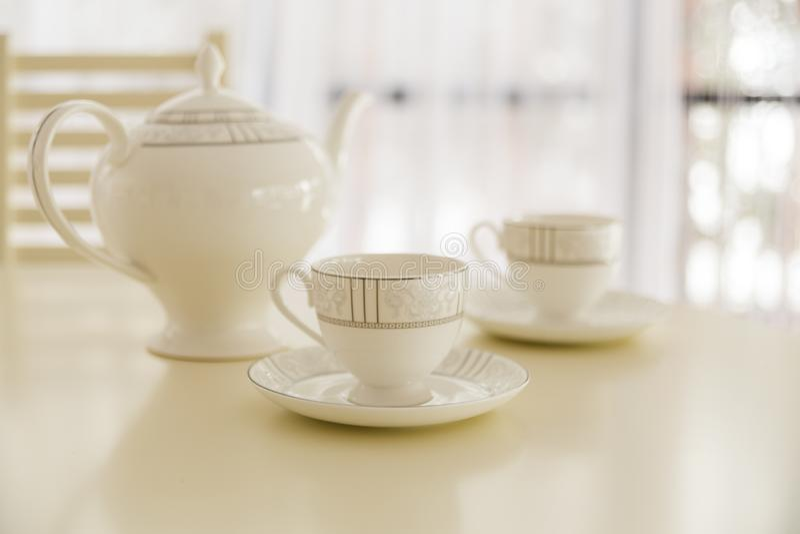 Vit kokkärl och två koppar för te på tabellen arkivbild