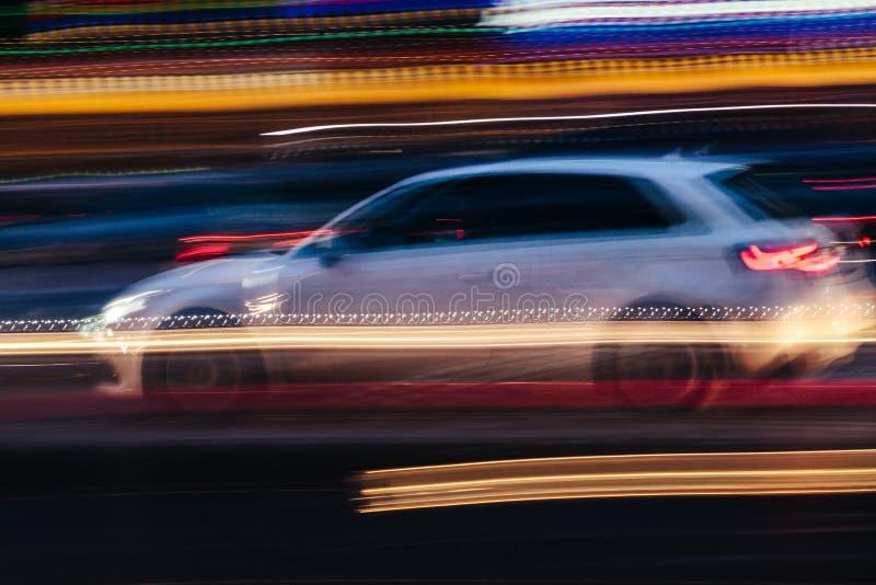 Vit kompakt bil i en suddig stadsplats royaltyfri fotografi