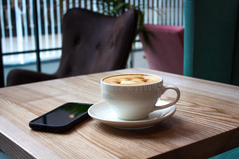 Vit kopp av cappuccino och den svarta mobiltelefonen royaltyfria foton