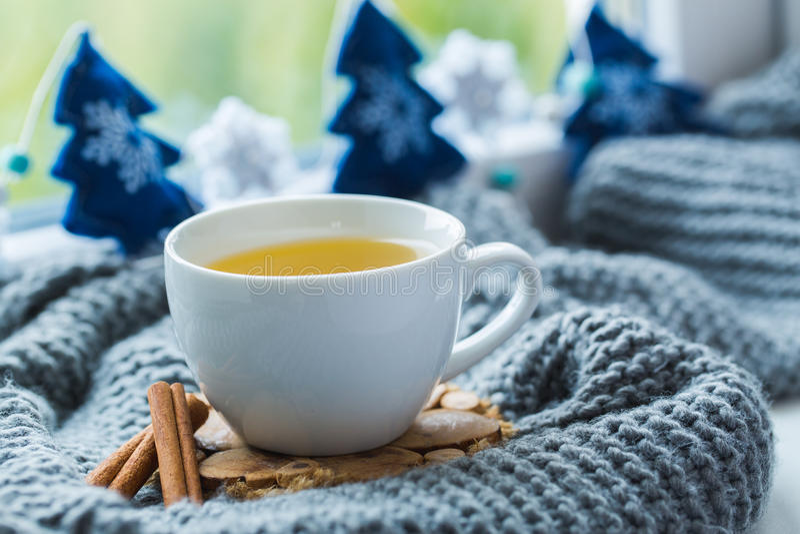 Vit kopp av kamomillte med den gråa halsduken på fönsterbrädan royaltyfria foton