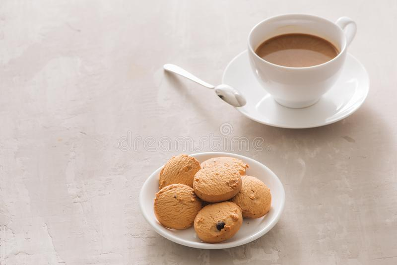 Vit kopp av krämigt kaffe med smörkakor och den rostfria teskeden som isoleras på vit bakgrund, snabb bana royaltyfria foton