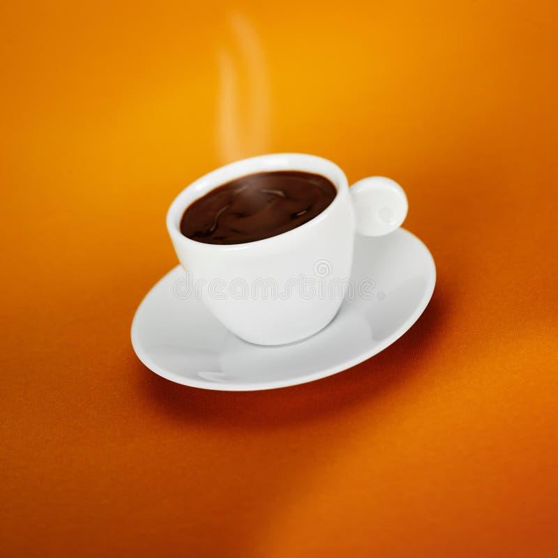 Vit kopp av varm mörk choklad på en orange bakgrund royaltyfri foto