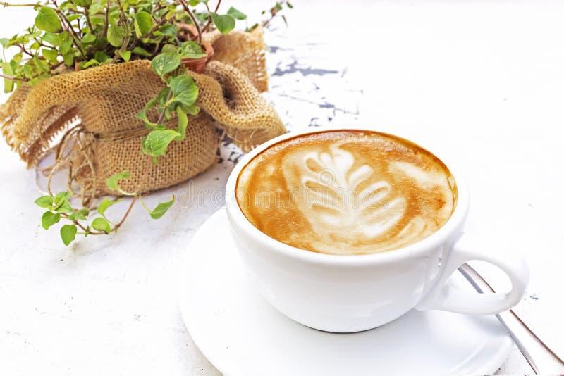 Vit kopp av varmt kaffe på trä med tabell- och växtkrukan på bakgrund fotografering för bildbyråer