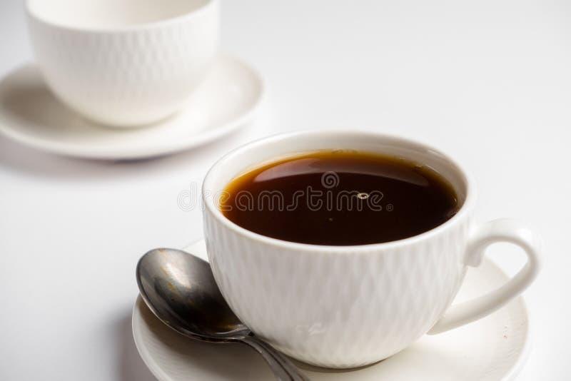 Vit kopp för kaffe med en sked på en vit bakgrund arkivfoto
