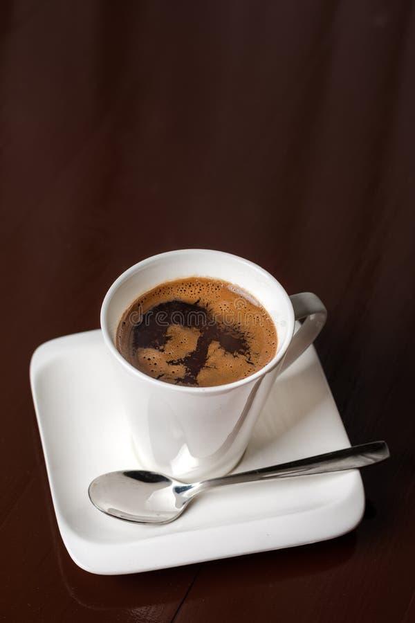 Vit kopp kaffe på den bruna trätabellen med kopieringsutrymme och mörkerbakgrund arkivfoton