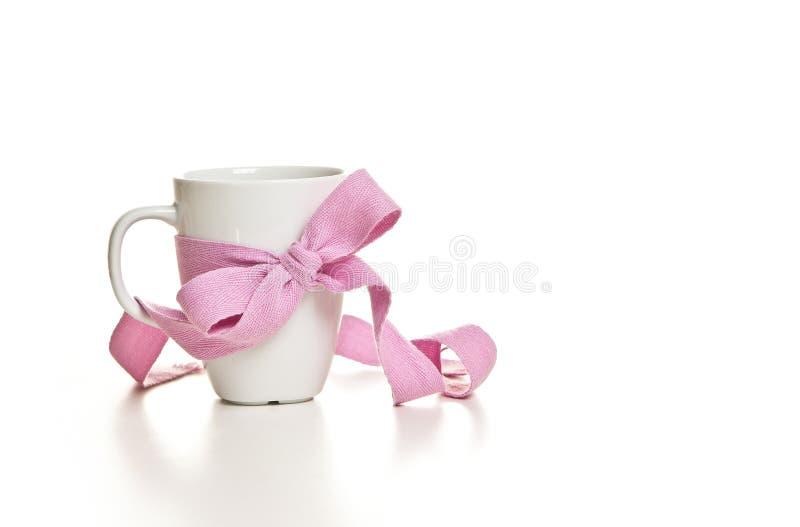 Vit kopp med en rosa flätad tråd arkivbild