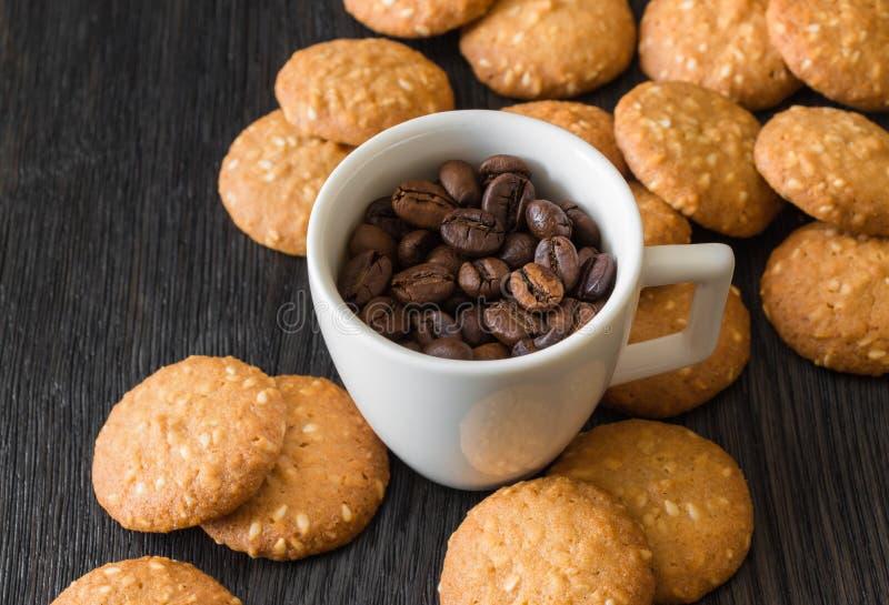 Vit kopp med grillade kaffebönor, kex med sesamfrö på en svart bakgrund royaltyfri fotografi