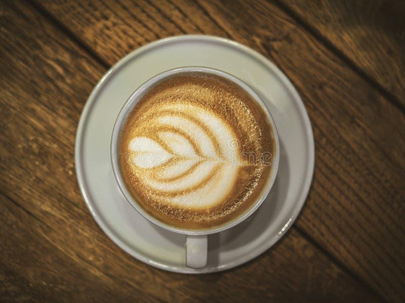 Vit kopp med kaffe på den gamla trätabellen i kafét fotografering för bildbyråer