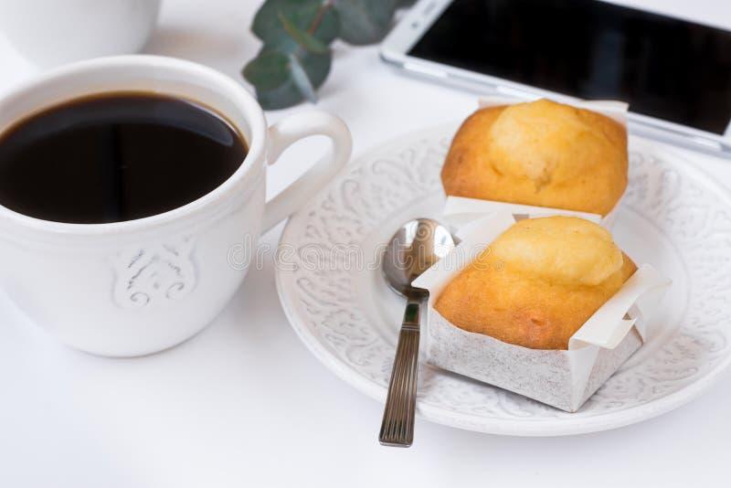 Vit kopp med kaffe, smartphone, bakelse på plattan, eukalyptusfilial på tabellen, affärsfrukost, kvinnlig utformad bild arkivfoto