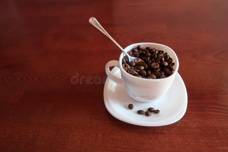 Vit kopp med kaffebönor inom och skeden arkivfoton
