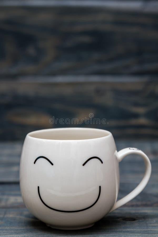 Vit kopp med Smiley Face på den blåa trätabellen arkivbild