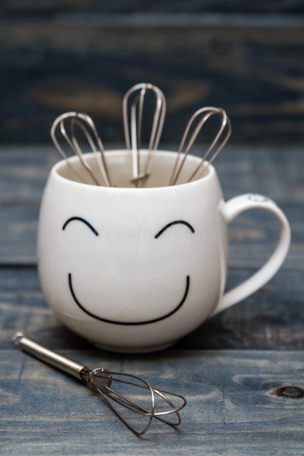 Vit kopp med Smiley Face på den blåa trätabellen arkivfoto