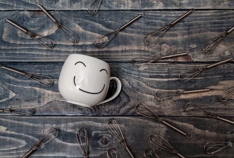 Vit kopp med Smiley Face på den blåa trätabellen royaltyfri foto