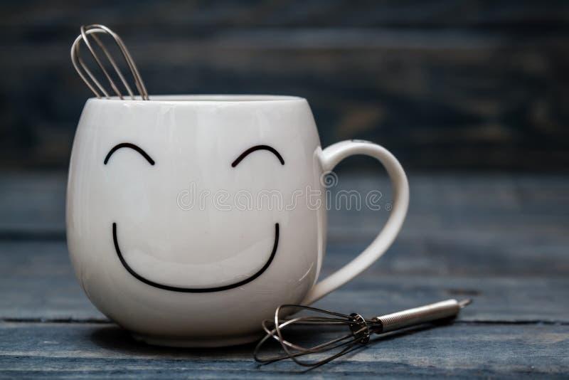 Vit kopp med Smiley Face på den blåa trätabellen royaltyfria bilder