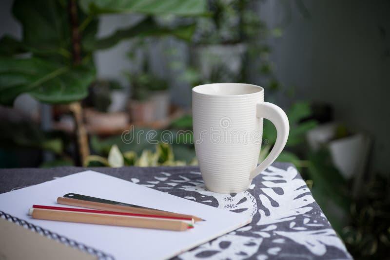 Vit kopp och en bok i trädgård royaltyfri bild